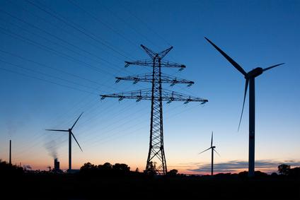 Strommast und Windräder in der Abenddämmerung